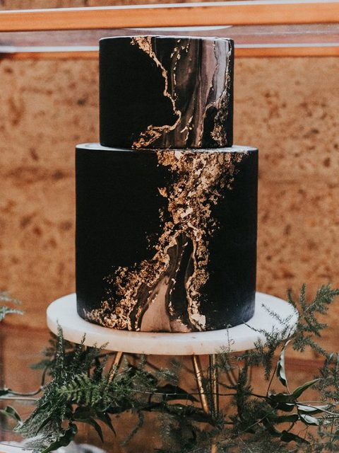a black wedding cake with copper marble detailing