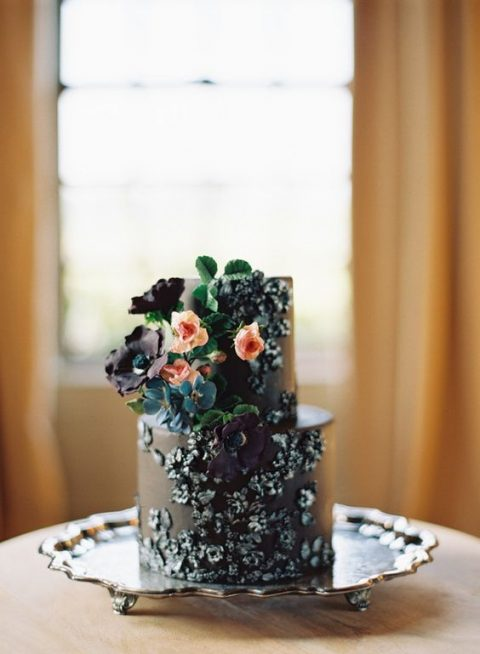 a black wedding cake with edible florals attached and some blooms and greenery