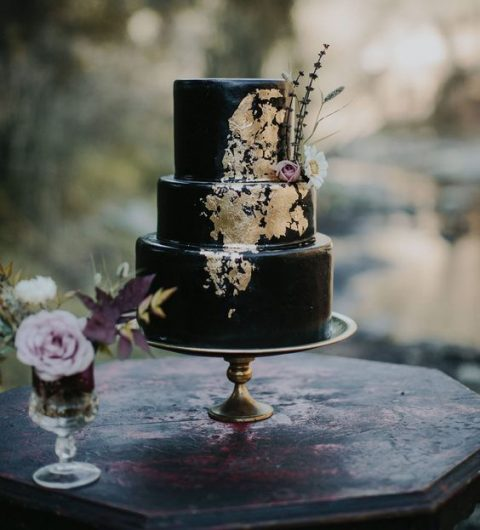 a black wedding cake with gold leaf and feathers