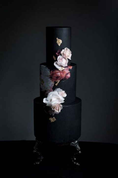 a black wedding cake withwatercolor flowers painted and fresh ones on top