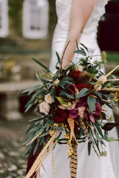 a bold bouquet with feather_ greenery_ burgundy roses and blush blooms