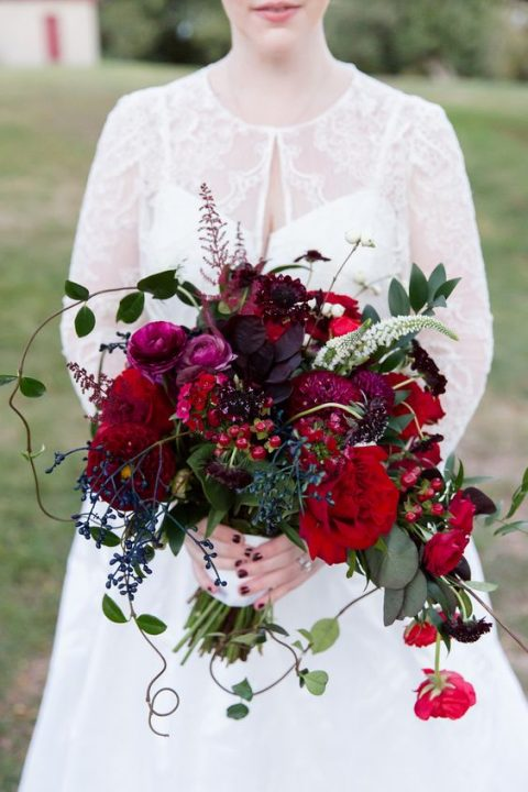 a bold bouquet with plum and red blooms_ dark foliage and privet berries