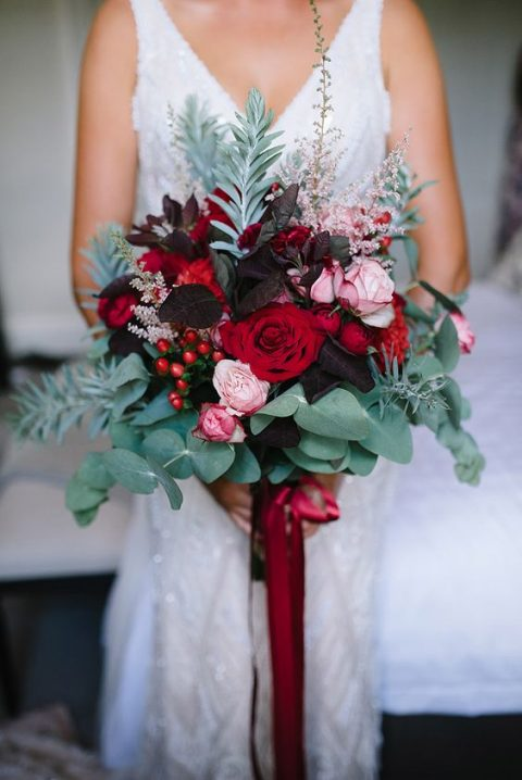 a bold wedding bouquet with dark leaves_ red and pink blooms_ eucalyptus and other greenery and red ribbons