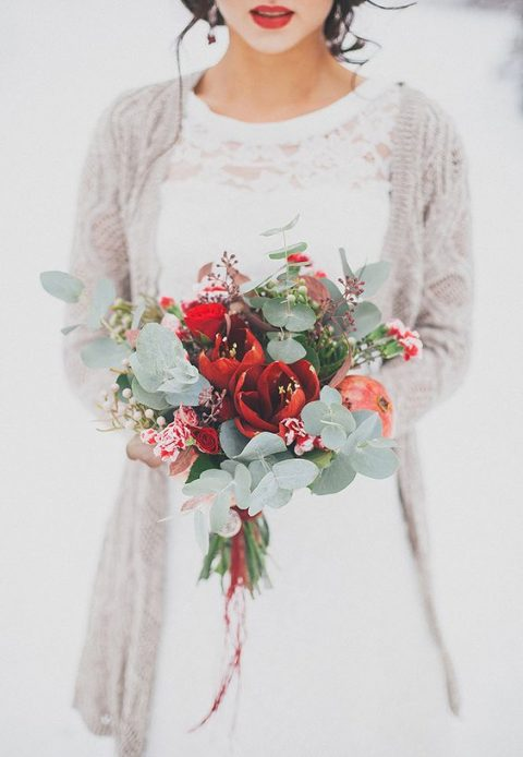 a bouquet of red blooms and eucalyptus with red ribbons