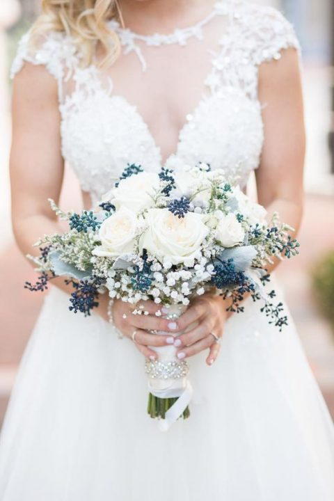 a bouquet of white roses_ privet berries and baby_s breath plus pale leaves