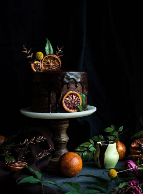 a chocolate wedding cake with chocolate drip_ leaves and orange slices