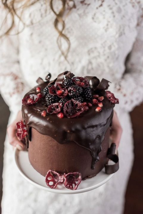 a chocolate wedding cake with chocolate dripping_ blackberries and pomegranate