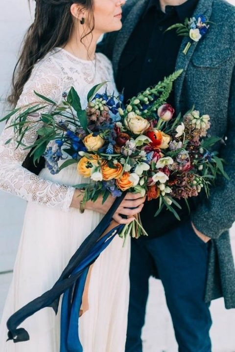 a colorful bouquet in blue_ yellow and orange with greenery and blue ribbons