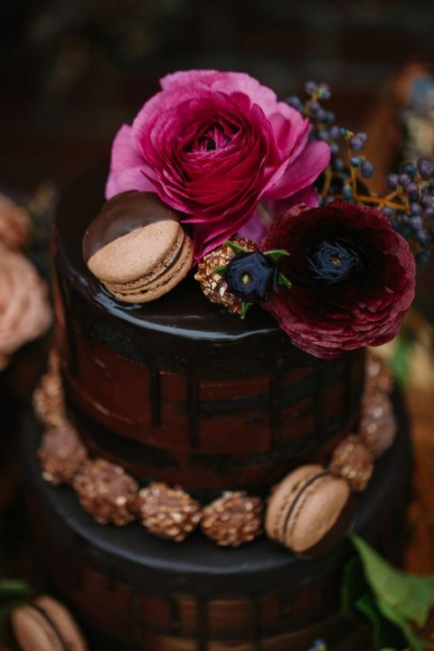 a dark wedding cake with chocolate dripping_ macarons and fuchsia blooms