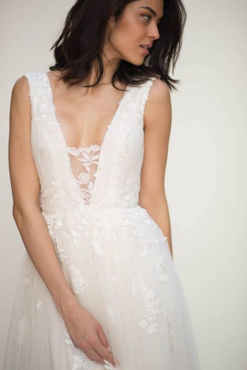 a floral applique wedding dress with an illusion plunging neckline