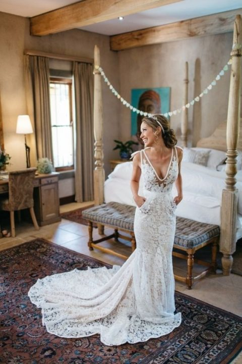 a lace mermaid wedding dress with a train_ a plunging neckline and pockets