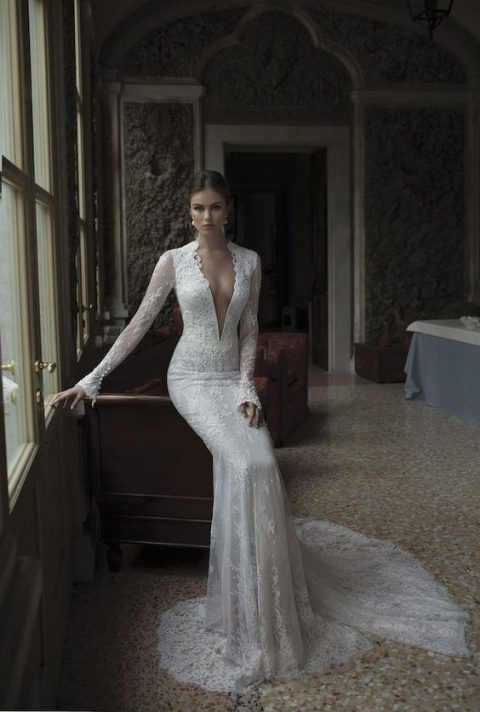 a long sleeve plunging neckline lace wedding dress with a mermaid silhouette and a train