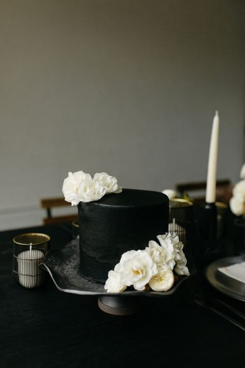 a matte black cake topped with fresh white blooms
