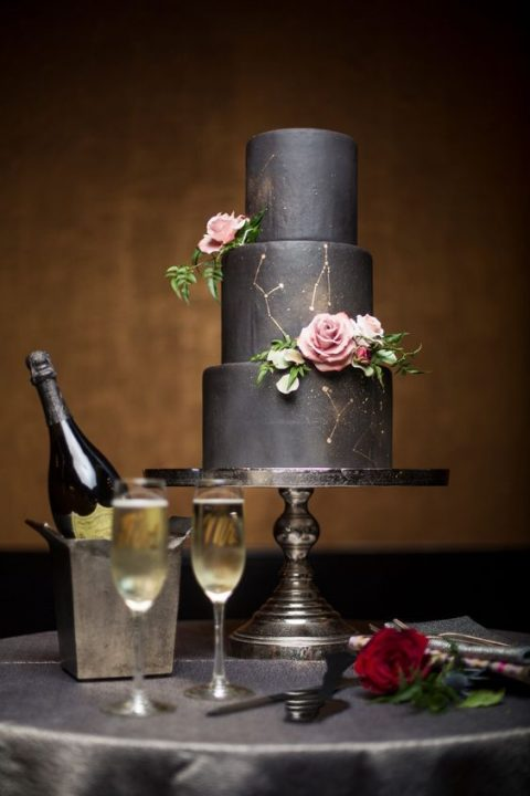 a matte black wedding cake with constellation decor and pink roses