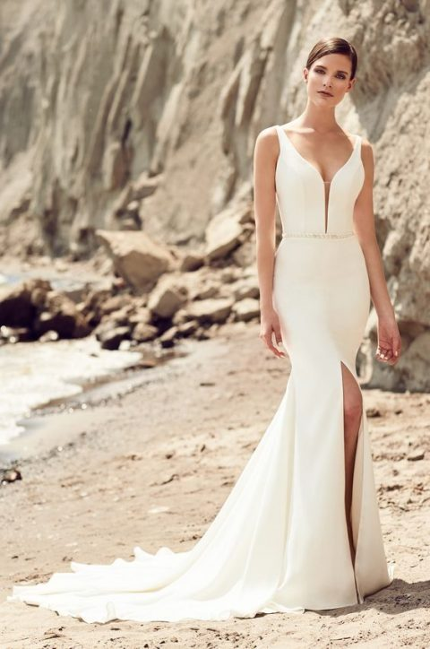 a modern mermaid wedding dress with straps_ a covered plunging neckline and a front slit