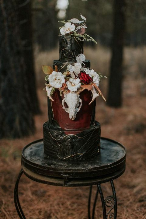 a moody boho wedding cake with textural layers_ lush blooms and a skull