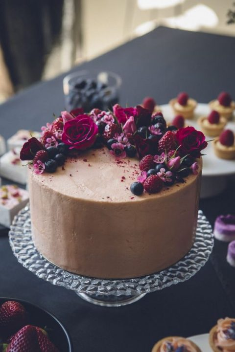 a moody chocolate frosted cake topped with fresh berries and bold blooms