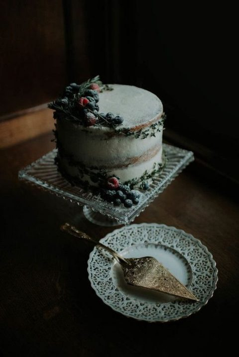 a moody naked wedding cake topped with sugared berries and rosemary
