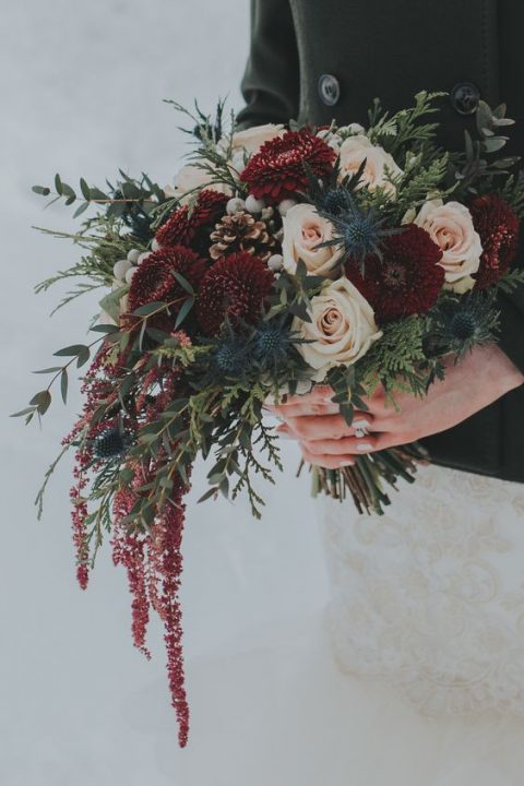 a moody winter bouquet with burgundy dahlias_ blush roses_ thistles_ pinecones_ berries and amaranthus