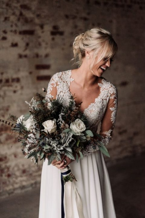 a moody winter bouquet with dusty miller_ feathers_ white roses_ thistles and evergreens