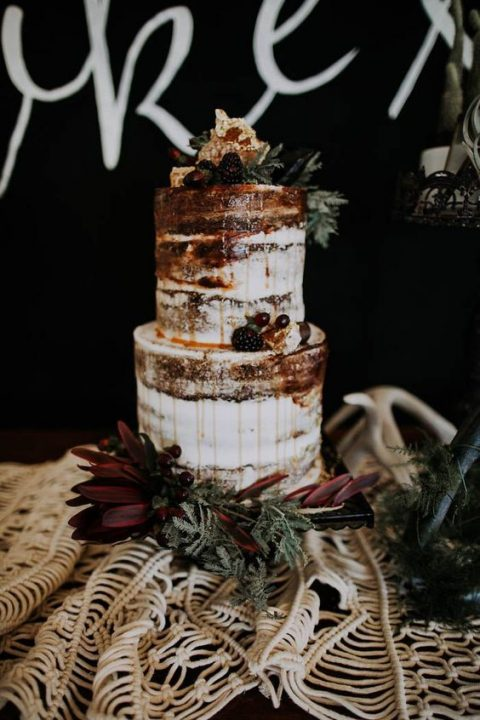 a naked wedding cake with dripping_ beries and greenery