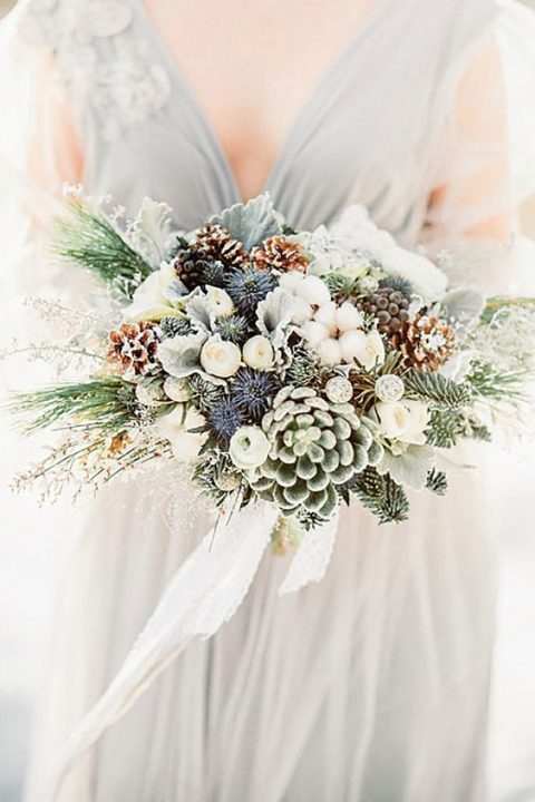 a neutral wedding bouquet with succulents_ pale leaves_ thistles_ pinecones and greenery