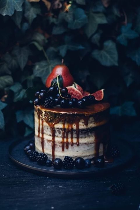 a semi naked wedding cake with caramel dripping_ blackberries_ blueberries and figs