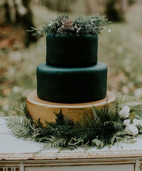 a three-tier wedidng cake with two black layers and a gold one_ topped with greenery