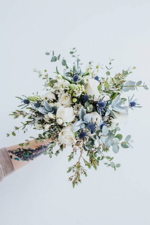 an ethereal bouquet with blue thistles_ white roses and pale leaves