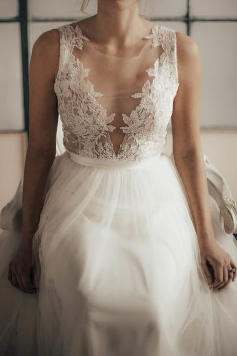 an ethereal wedding dress with a sleeveless lace wedding bodice_ a covered plunging neckline and a layered skirt