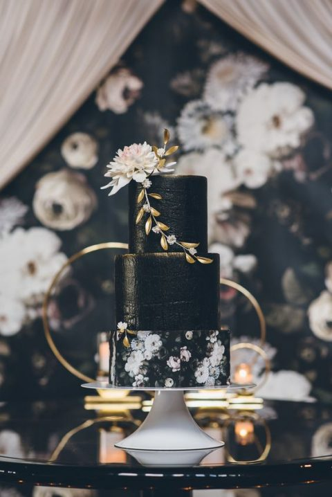 black textural wedding cake with a floral layer and a blush bloom on top