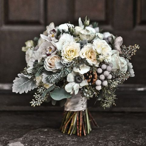 mini cymbidium orchids_ silver brunia_ juniper sprigs_ pine boughs_ anemones_ pinecones_ garden spray roses_ seeded eucalyptus_ blush roses_ and dusty miller