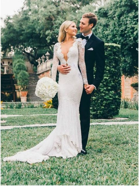 sheath lace wedding dress with a plunging neckline_ long sleeves and a train