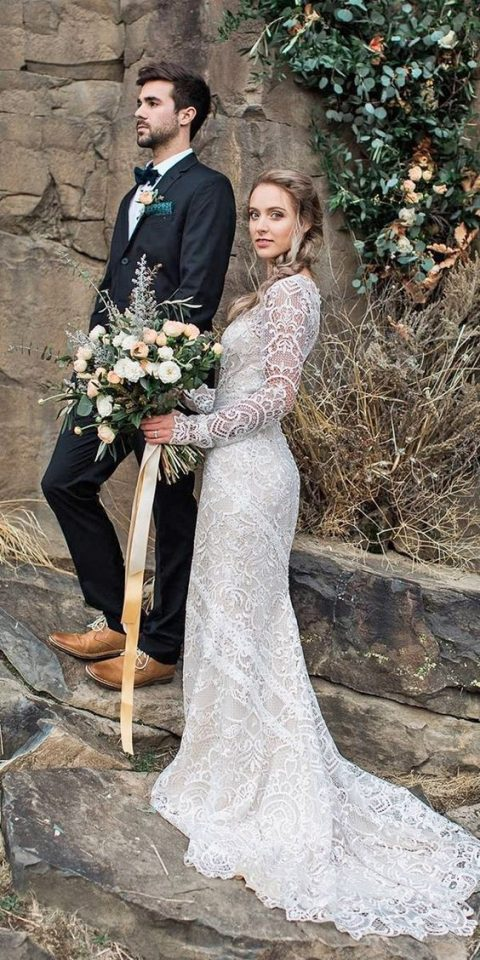 a boho lace wedding dress with long sleeves and a small train