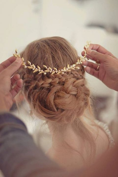 a braided low updo with a gold hairpiece