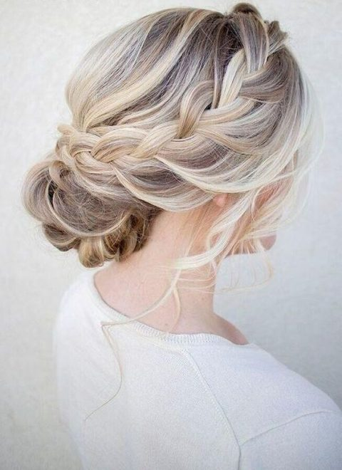 a braided low updo with waves looks interesting on balayage