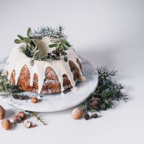 a bundt wedding cake with white chocolate dripping_ evergreens_ pinecones and sugar powder to imitate snow