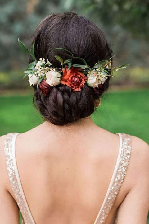 a chic braided low updo with fresh blooms and foliage