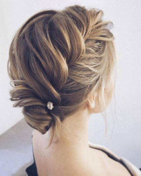 a chic braided updo with some locks down and a rhinestone pin