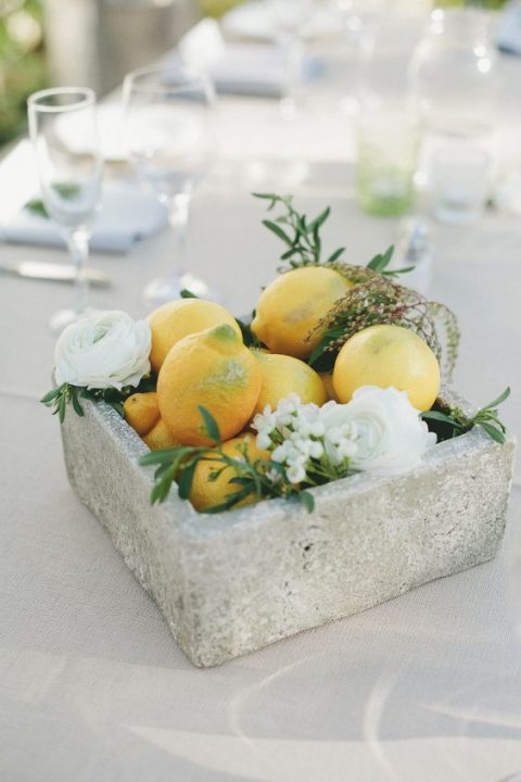 a concrete box with lemons and white blooms