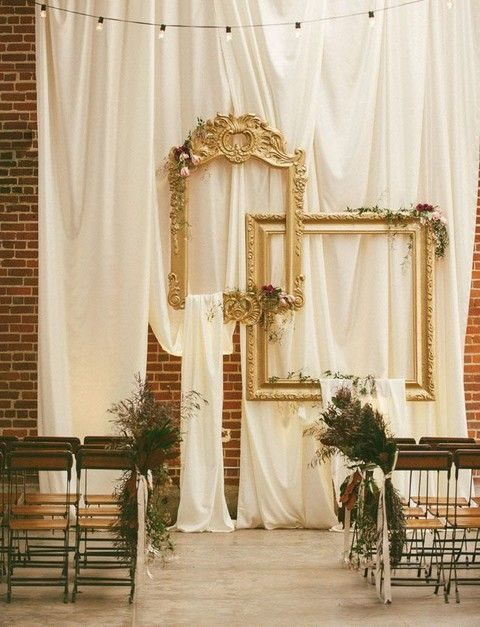 a draped fabric backdrop and a couple of vintage picture frames