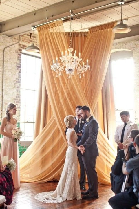 a draped fabric backdrop and a glam chandelier for a glam feel