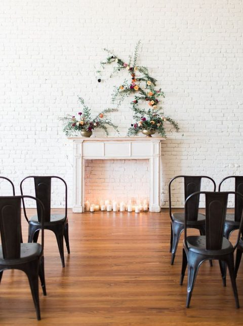 a faux fireplace and colorful floral arrangements_ some candles for a wedding backdrop