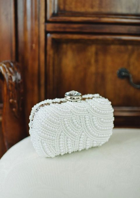 a glam pearly clutch with a large rhinestone on top
