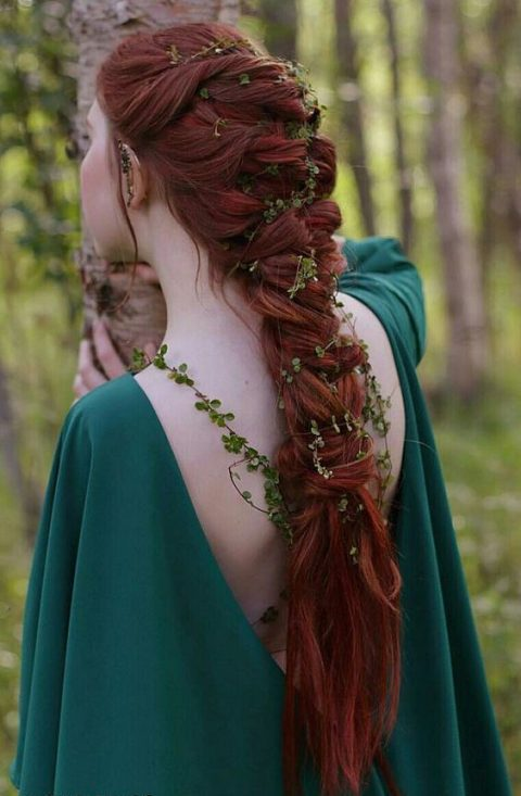 a large twisted braid on long red hair and fresh foliage