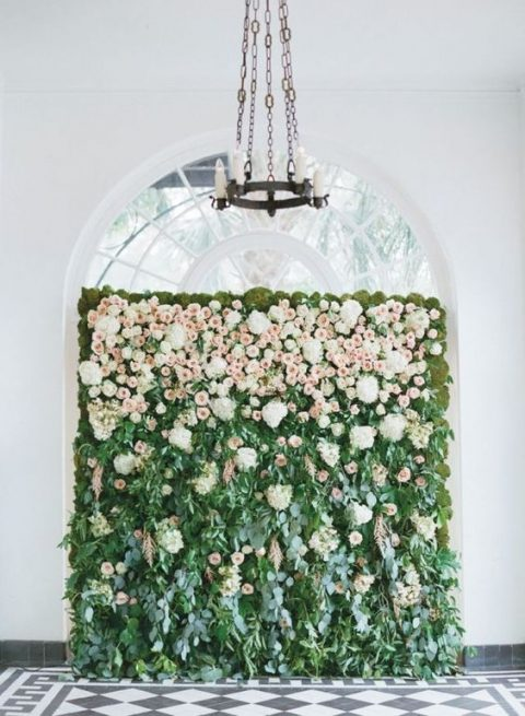 a living wall with lush white and blush blooms