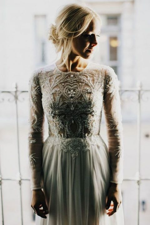 a long sleeve wedding gown with lace appliques and beads and a plain pleated skirt