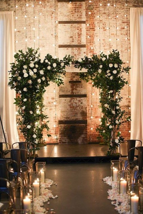 a lush greenery and white rose wedding arch and lights in front of a brick wall