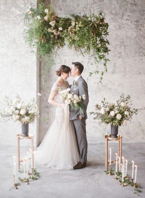 a lush greenery chandelier_ blooms and candles for a ceremony space