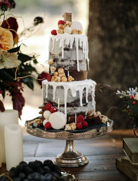 a luxurious semi naked wedding cake with raspberries_ macarons_ chocolate and creamy drip